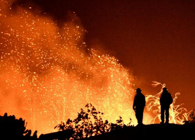 Firefighters keep watch on the Thomas wildfire in the hills and canyons outside Montecito, California